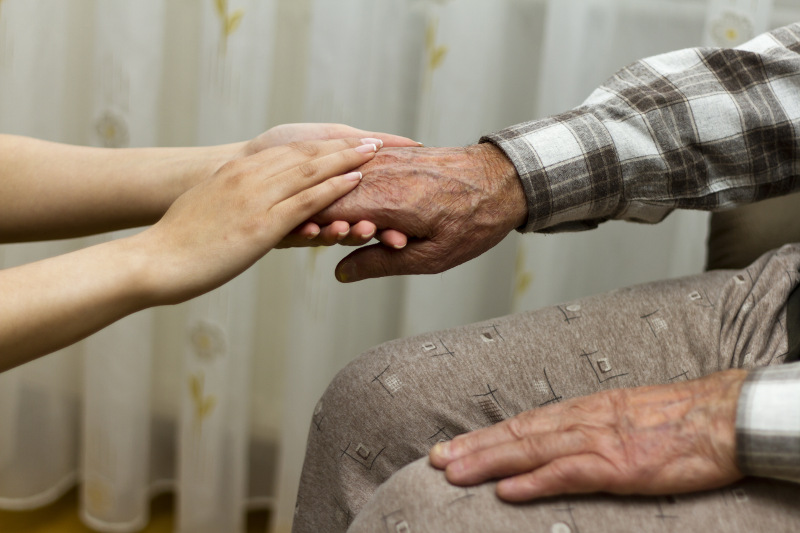 Seated elderly mans hands being held by younger woman's hands