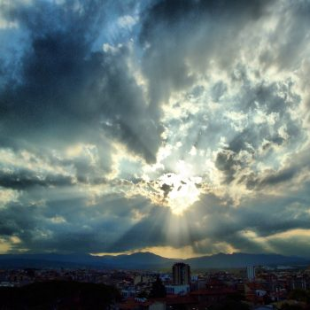 Sun shining through big sky of clouds