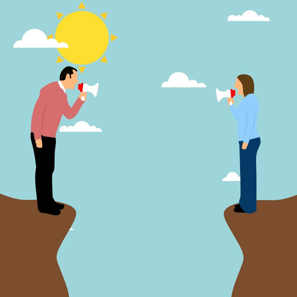 Man adn woman shouting at each other with megaphones across chasm